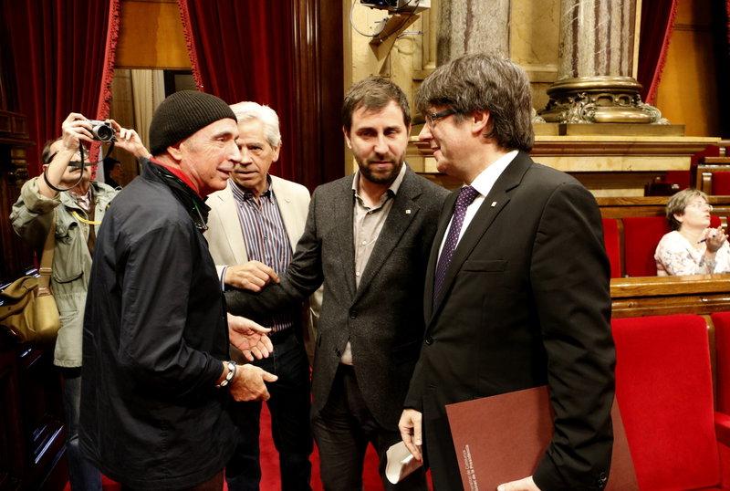 El president de la Generalitat, Carles Puigdemont, saluda el diputat de JxSí Lluís Llach, al ple del Parlament del 26 d'abril de 2017. (Horitzontal)