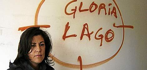La presidenta de Galicia Bilingüe, Gloria Lago, junto a una gran pintadarealizada por extremistas gallegos en la que le amenazan de muerte